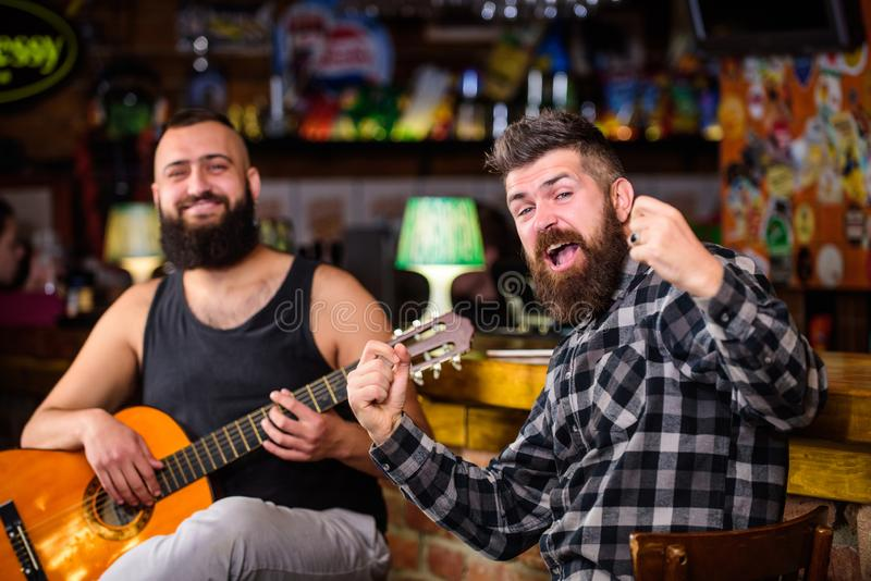 Man play guitar in pub. Live music concert. Acoustic performance in pub. Hipster brutal bearded with friend in pub. Cheerful friends sing song guitar music royalty free stock images