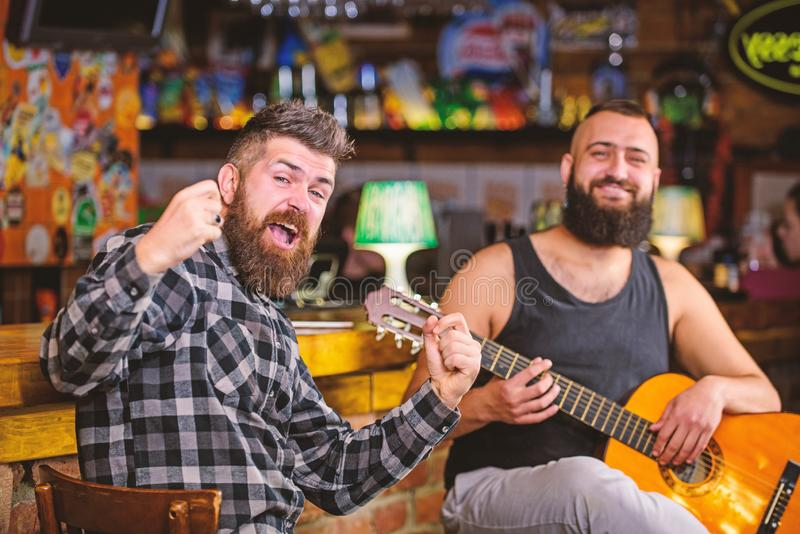 Man play guitar in pub. Live music concert. Acoustic performance in pub. Hipster brutal bearded with friend in pub. Cheerful friends sing song guitar music royalty free stock photography