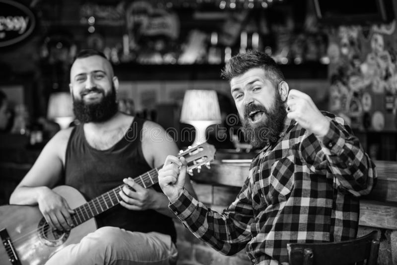 Man play guitar in pub. Live music concert. Acoustic performance in pub. Hipster brutal bearded with friend in pub. Cheerful friends sing song guitar music royalty free stock photos