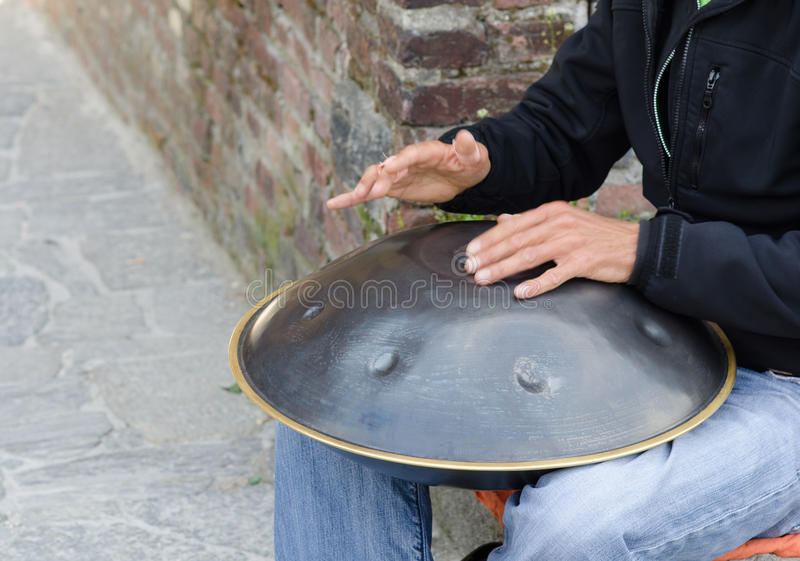 Man play instrument made of metal and called hang stock photography