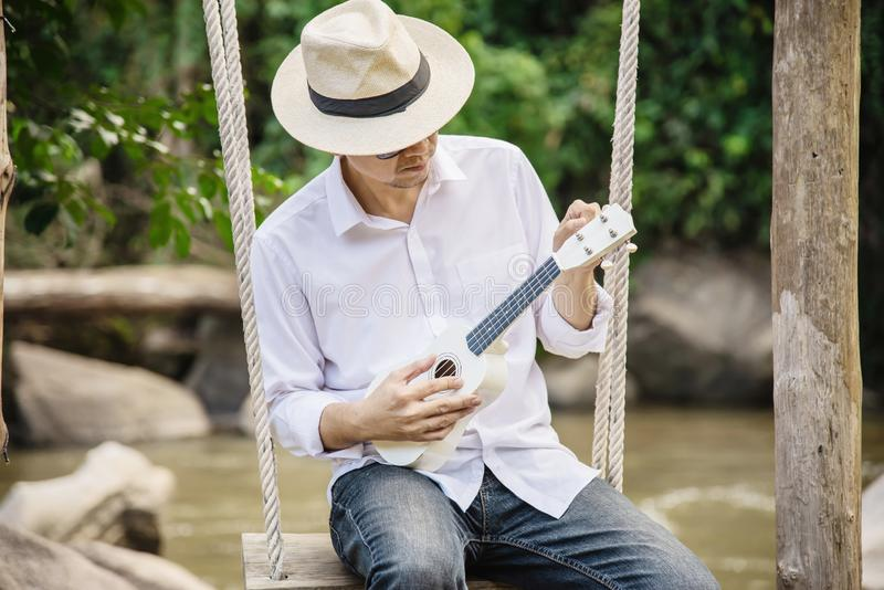 Man play ukulele new to the river stock photo