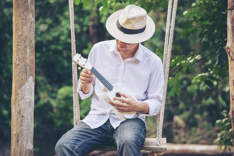 Man play ukulele new to the river- people and music instrument life style. In nature concept royalty free stock photo