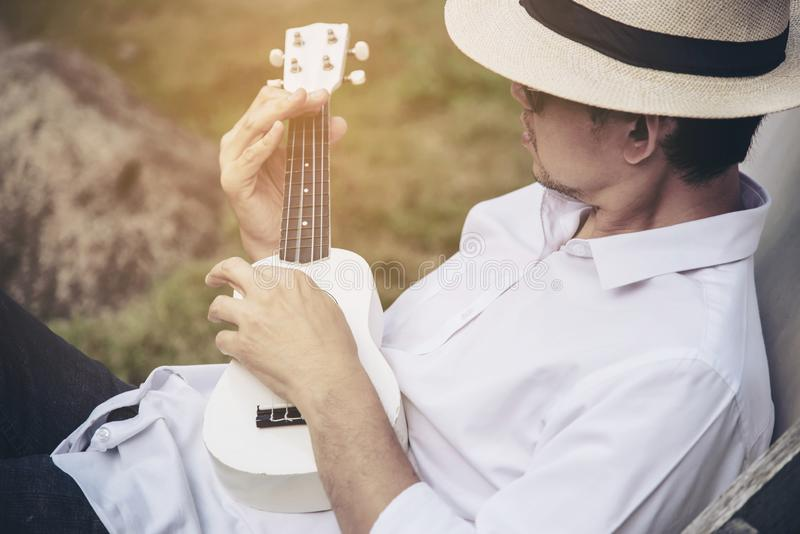 Man play ukulele new to the river- people and music instrument life style. Man play ukulele new to the river - people and music instrument life style in nature royalty free stock photography