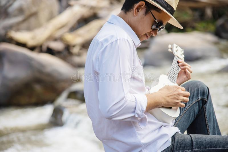 Man play ukulele new to the waterfall stock images