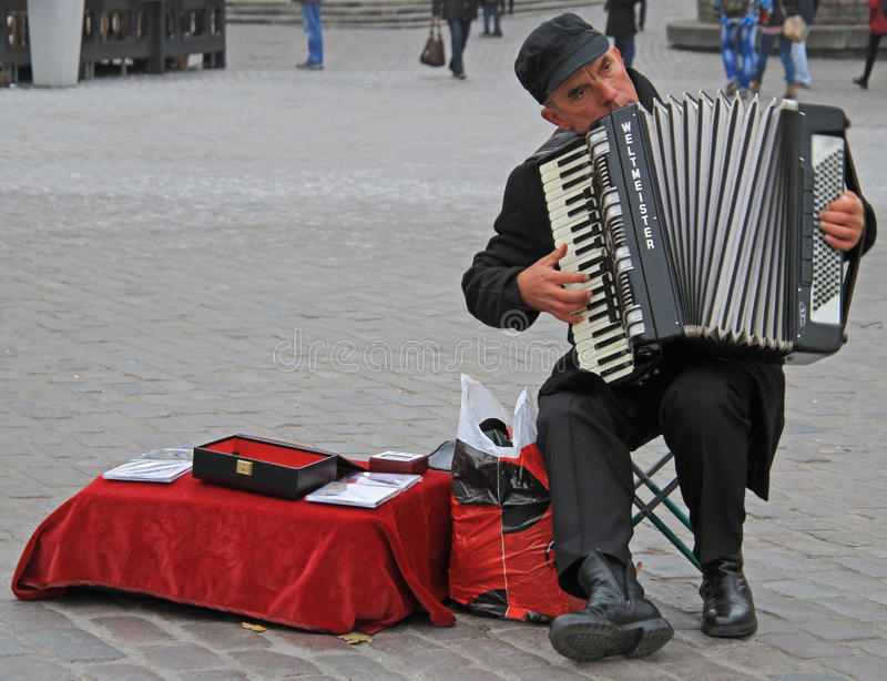 Man are playing the accordion at the square nearly Royal Castle in Warsaw royalty free stock photo