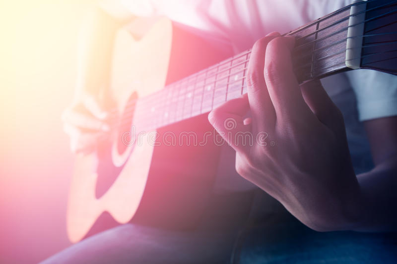 Man playing acoustic guitar in concert. Man in white t-shirt playing acoustic guitar in concert royalty free stock image