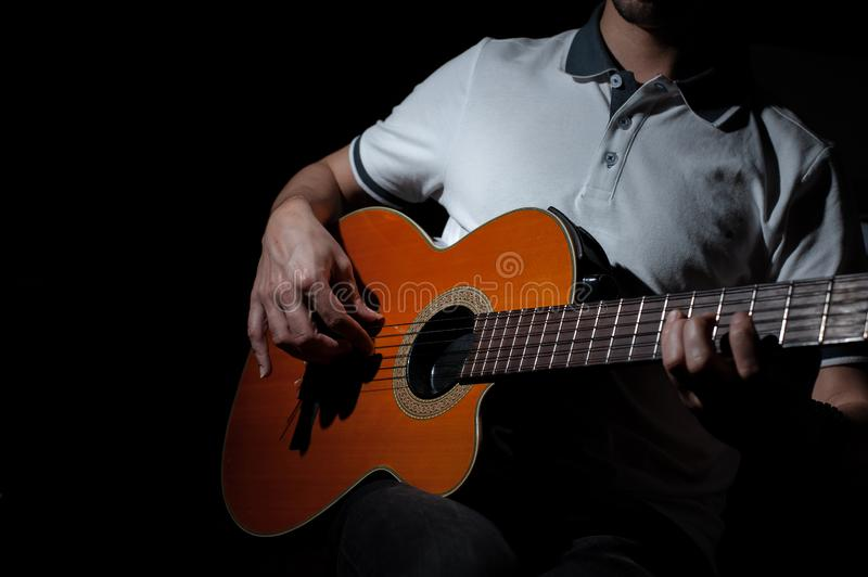 Man playing an acoustic guitar on a dark background. Playing guitar. Concert music musical male musician black guitarist performer string young instrument stock photography