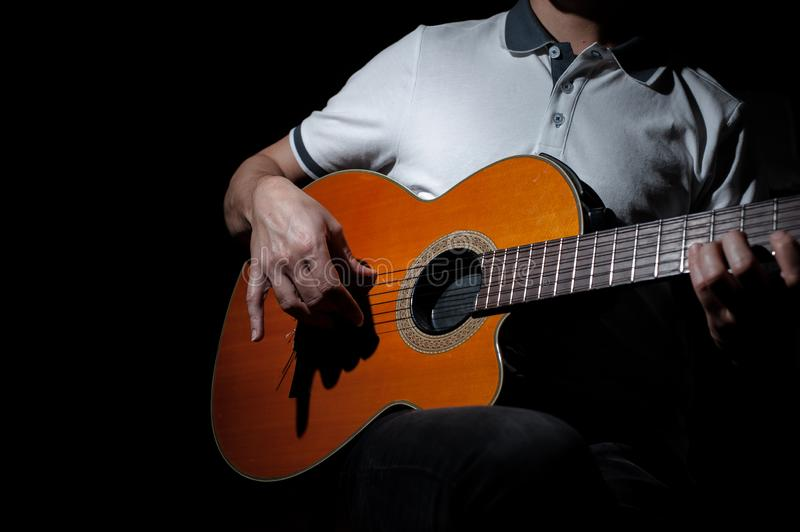 Man playing an acoustic guitar on a dark background. Playing guitar. Concert music musical male musician black guitarist performer string young instrument stock photos