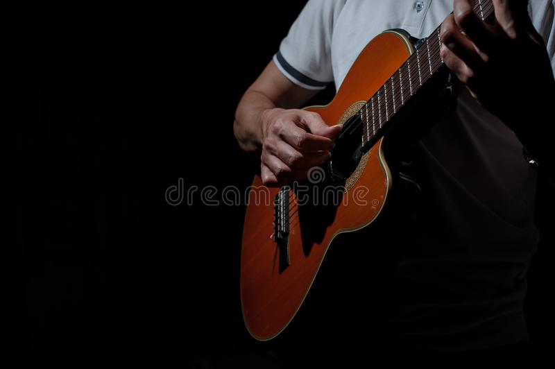 Man playing an acoustic guitar on a dark background. Playing guitar. Concert music musical male musician black guitarist performer string young instrument stock photo