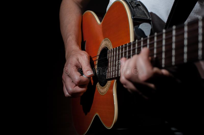 Man playing an acoustic guitar on a dark background. Playing guitar. Concert music musical male musician black guitarist performer string young instrument stock image