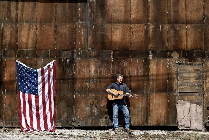 Man playing acoustic guitar in front of old warehouse building with American flag. In the city, Memorial Day, July 4th, Veteran's Day stock photos