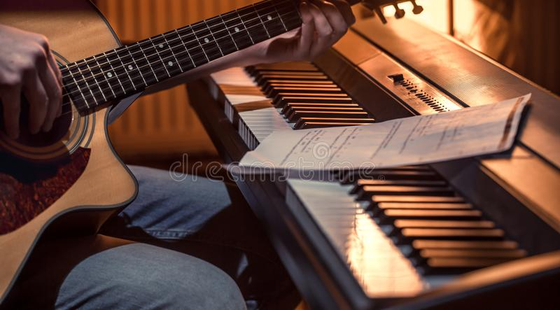 Man playing acoustic guitar and piano close-up, recording notes stock photos
