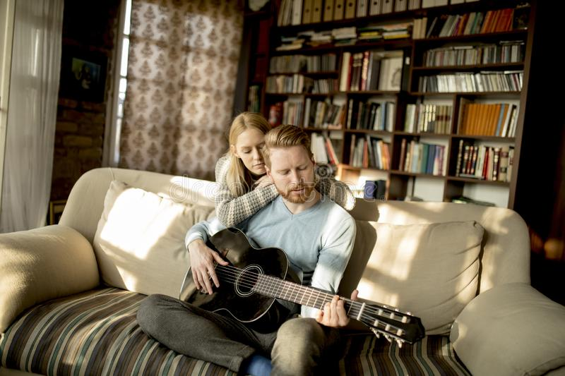 Man playing acoustic guitar on sofa for his young beautiful woman stock photo