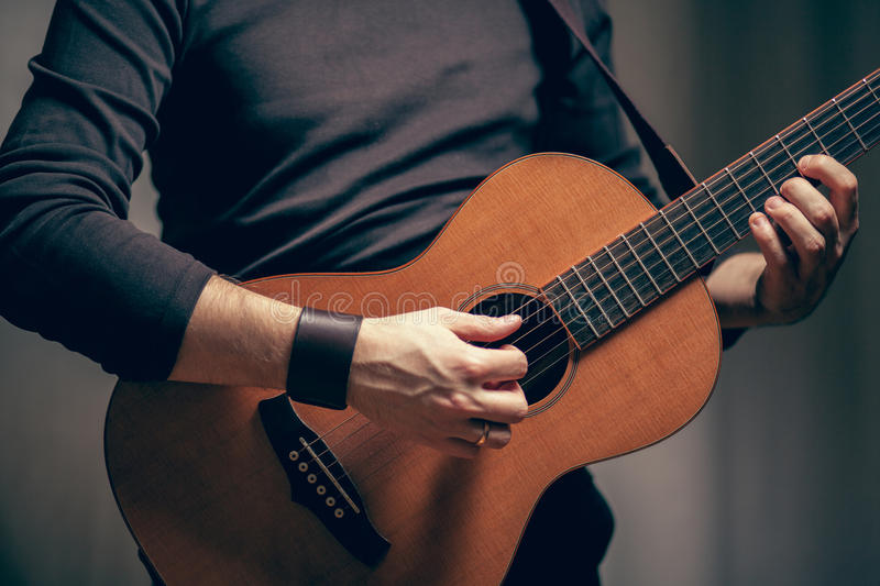 A man is playing on acoustic vintage guitar stock image