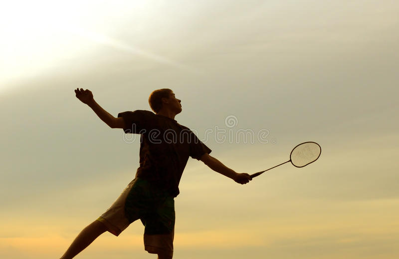 Man playing badminton. Silhouette of badminton player against evening sky stock photo