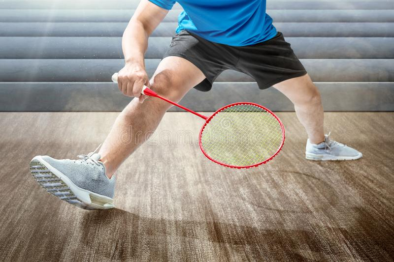 Man playing badminton with badminton racket. On the indoor court stock image