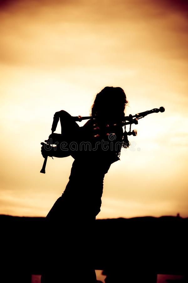 Man Playing The Bagpipe. Silhouette of man playing the bagpipe royalty free stock image