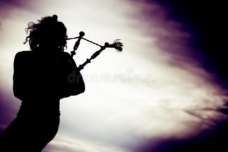 Man Playing The Bagpipe. Silhouette of man playing the bagpipe royalty free stock photography