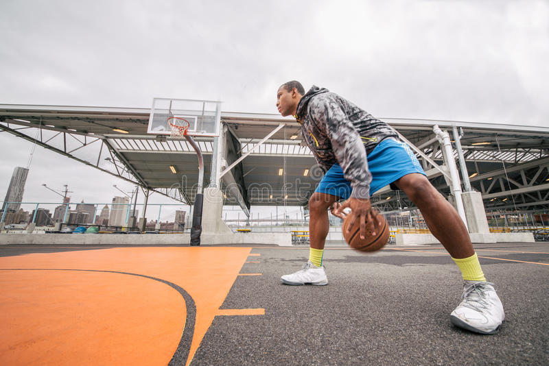 Man playing basketball. Afroamerican player playing basketball outdoors - Sportive man training in a basketball court royalty free stock image