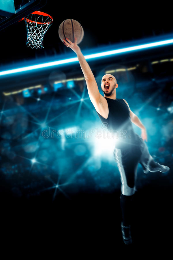 Man playing basketball and makes slam dunk on game stock image