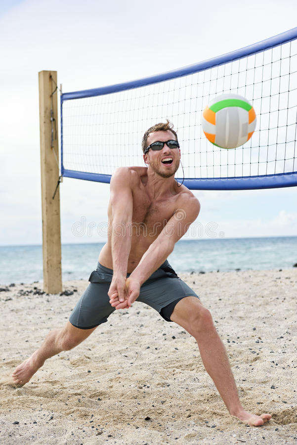 Man playing beach volleyball game hitting ball. Man playing beach volleyball game hitting forearm pass volley ball on summer beach. Male model living healthy royalty free stock image