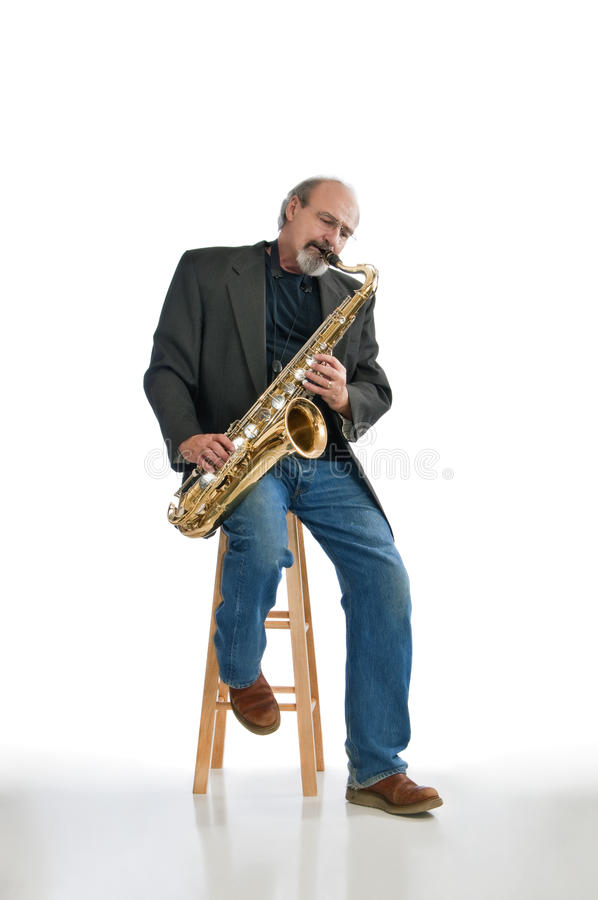 Man playing blues on a tenor sax. Adult male playing a tenor saxaphone while seated isolated on pure white stock photos