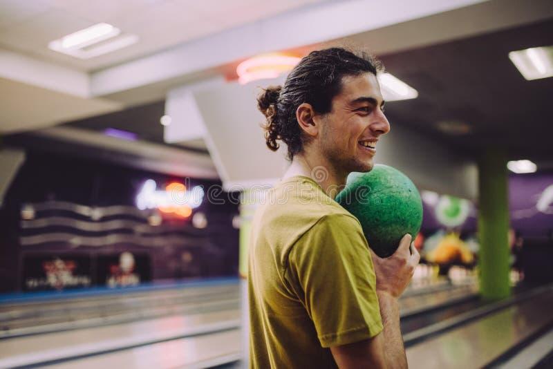 Man playing at bowling alley stock image