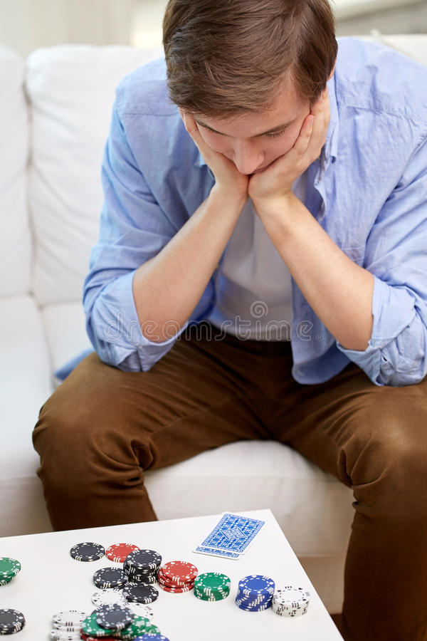 Man with playing cards and chips at home stock photos