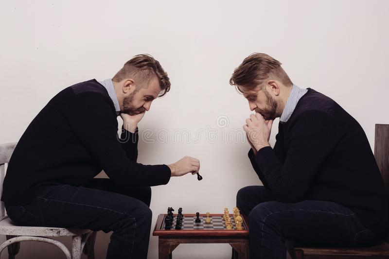 Man playing chess against himself stock photos