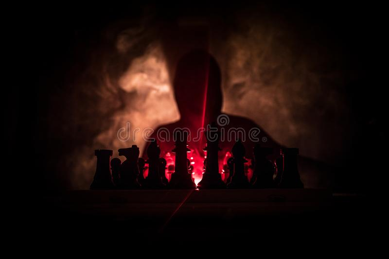 Man playing chess. Scary blurred silhouette of a person at the chessboard with chess figures. Dark toned foggy background. Selective focus. Horror concept royalty free stock image