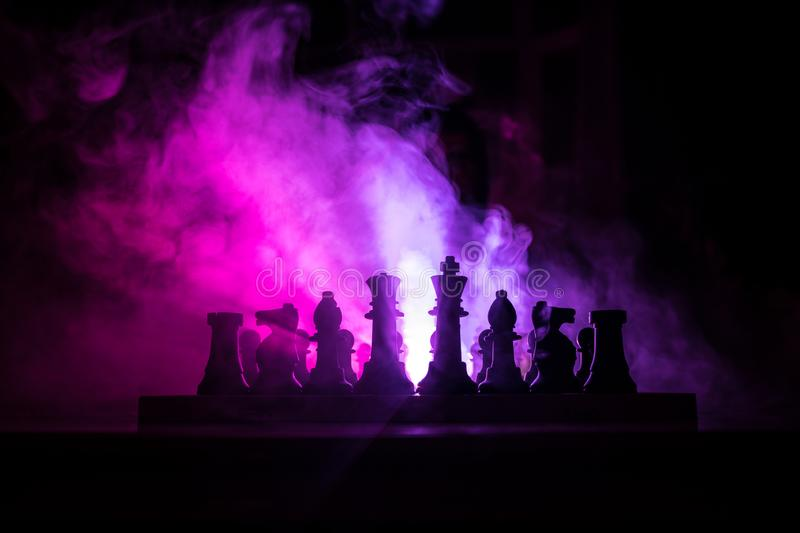 Man playing chess. Scary blurred silhouette of a person at the chessboard with chess figures. Dark toned foggy background. Selective focus. Horror concept royalty free stock photography