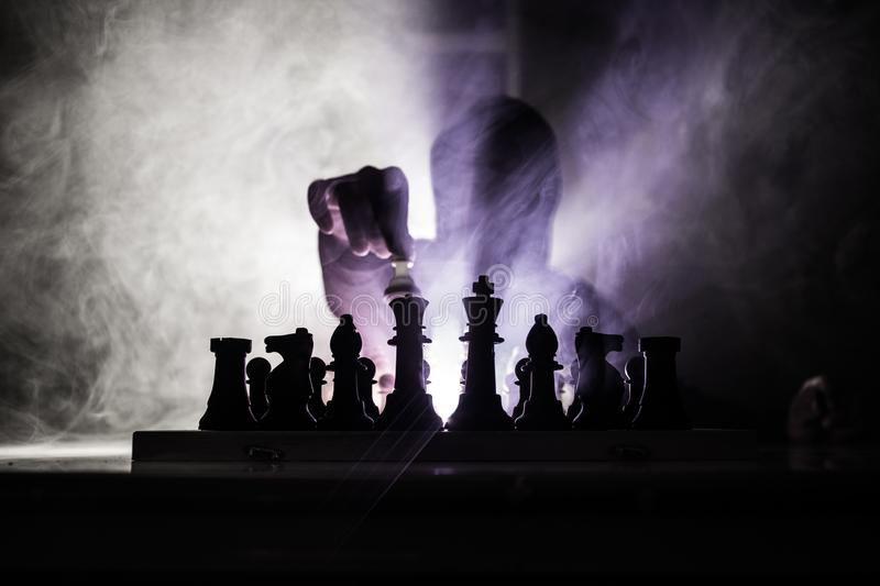 Man playing chess. Scary blurred silhouette of a person at the chessboard with chess figures. Dark toned foggy background. stock images
