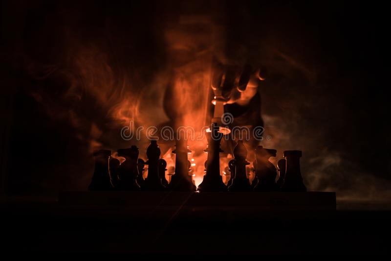 Man playing chess. Scary blurred silhouette of a person at the chessboard with chess figures. Dark toned foggy background royalty free stock photo