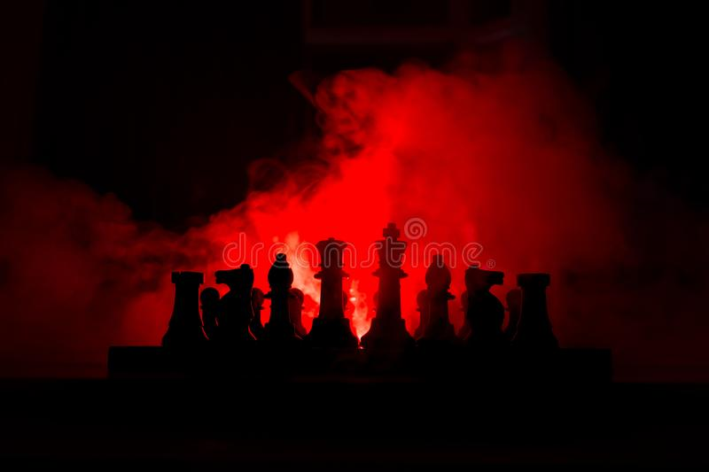 Man playing chess. Scary blurred silhouette of a person at the chessboard with chess figures. Dark toned foggy background stock photo
