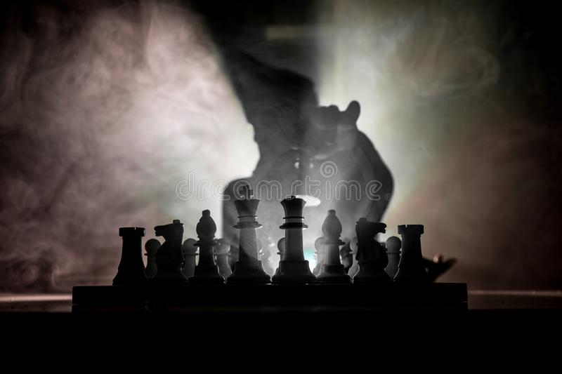 Man playing chess. Scary blurred silhouette of a person at the chessboard with chess figures. Dark toned foggy background. Selective focus. Horror concept royalty free stock images