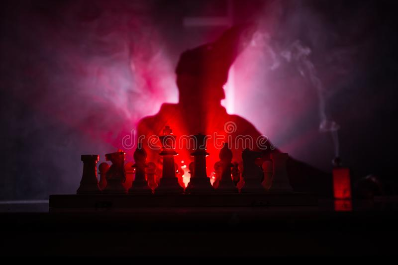 Man playing chess. Scary blurred silhouette of a person at the chessboard with chess figures. Dark toned foggy background. Selective focus. Horror concept stock image