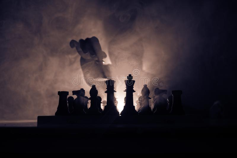 Man playing chess. Scary blurred silhouette of a person at the chessboard with chess figures. Dark toned foggy background. Selective focus. Horror concept royalty free stock photos