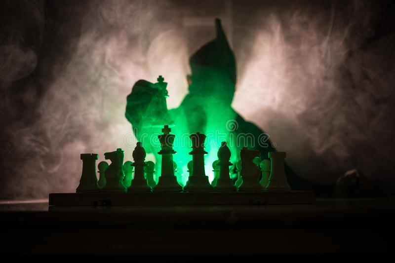 Man playing chess. Scary blurred silhouette of a person at the chessboard with chess figures. Dark toned foggy background. Selective focus. Horror concept stock photos