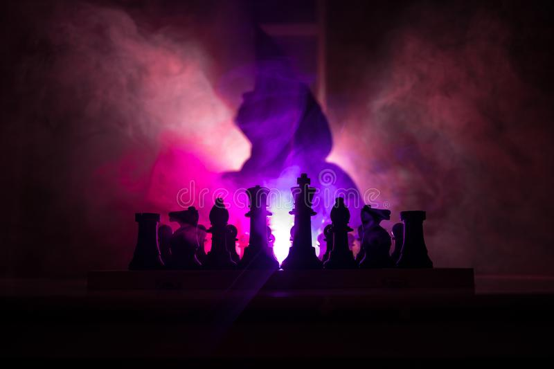 Man playing chess. Scary blurred silhouette of a person at the chessboard with chess figures. Dark toned foggy background. Selective focus. Horror concept royalty free stock photo