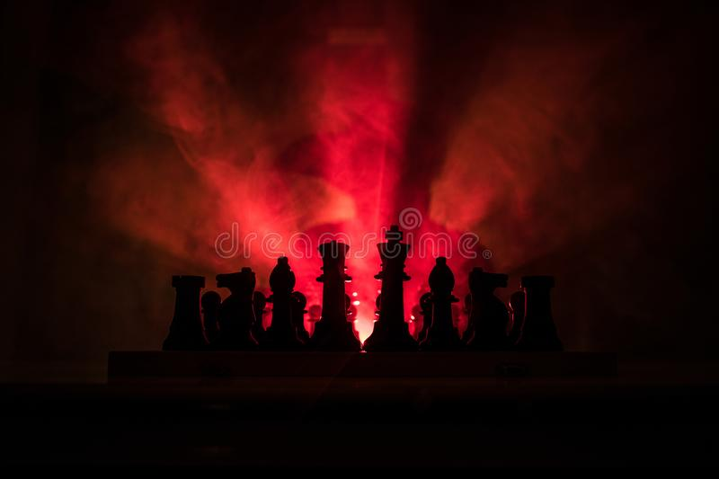 Man playing chess. Scary blurred silhouette of a person at the chessboard with chess figures. Dark toned foggy background. Selective focus. Horror concept stock photography