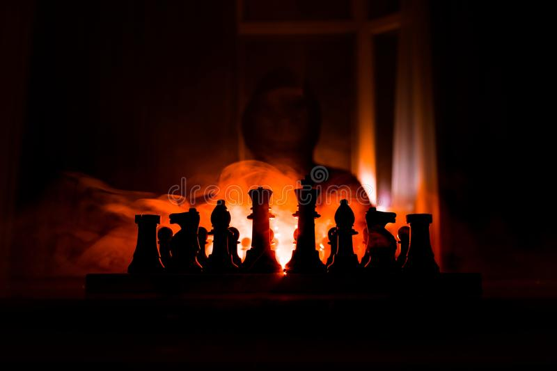 Man playing chess. Scary blurred silhouette of a person at the chessboard with chess figures. Dark toned foggy background stock images