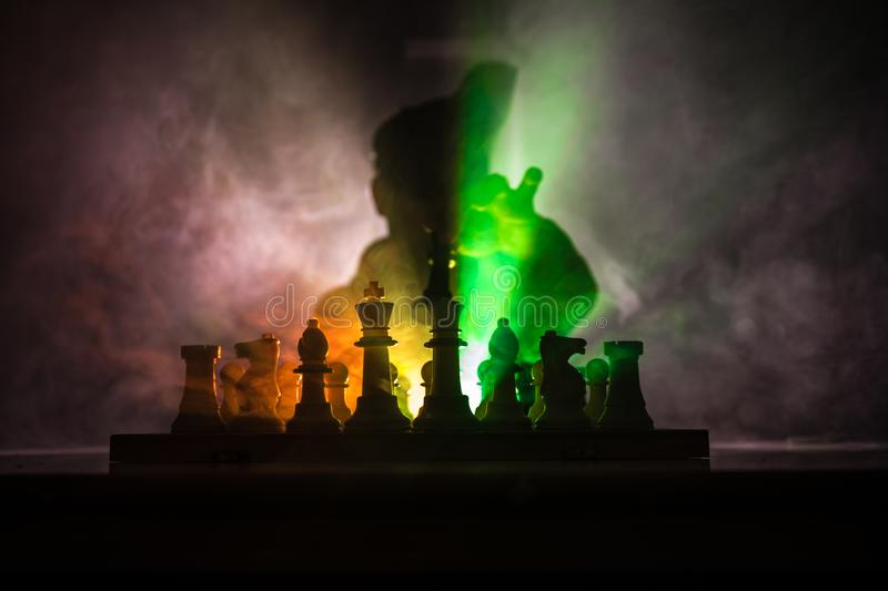 Man playing chess. Scary blurred silhouette of a person at the chessboard with chess figures. Dark toned foggy background stock photography