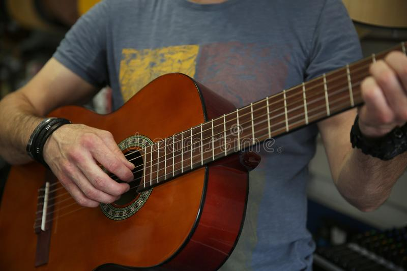 Man playing a classic guitar. Hand picks up the strings on the guitar. stock image