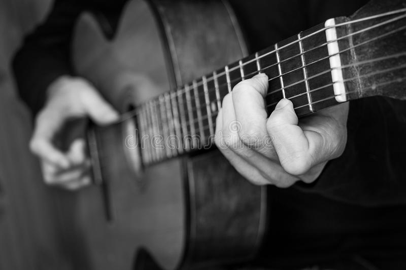 Man playing classical guitar. Black and white photo. royalty free stock image