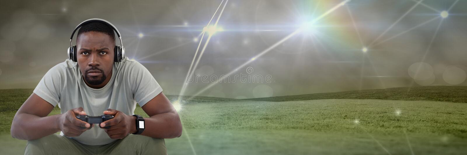 Man playing with computer game controller with light connections on green hills background. Digital composite of man playing with computer game controller with stock illustration
