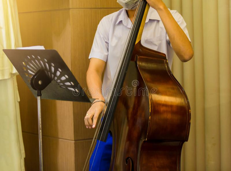 Man playing contra-bass with music notation. Double bass performer. Musician with string instrument on stage. Classic concert royalty free stock photos