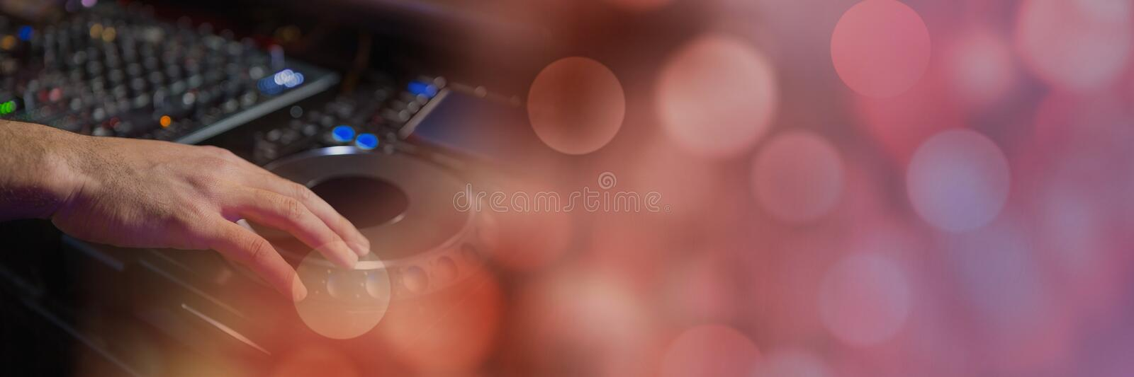 Man playing DJ equipment with pink lights. Digital composite of Man playing DJ equipment with pink lights stock photos