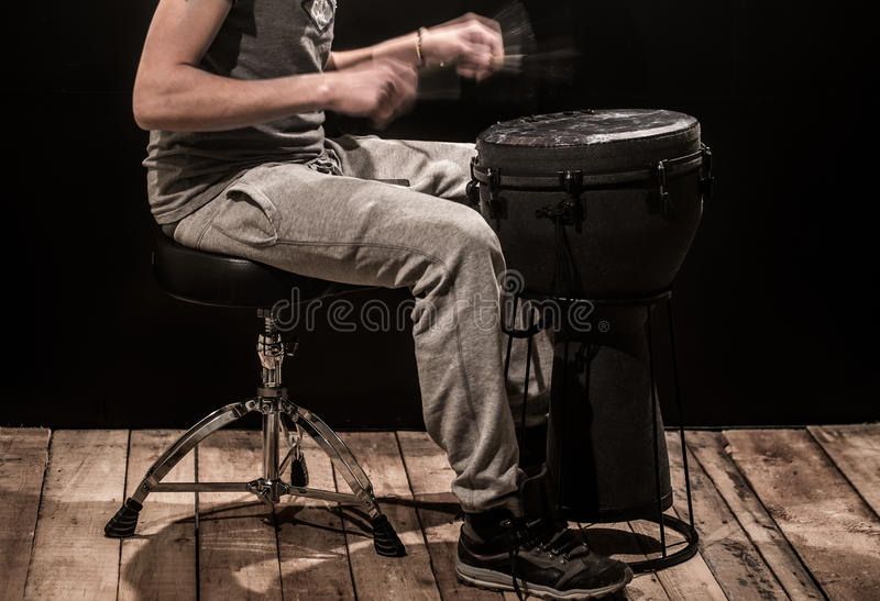 Man playing a djembe drum and cymbals on a black background royalty free stock photography