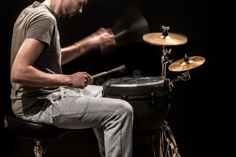 Man playing a djembe drum and cymbals on a black background royalty free stock photos