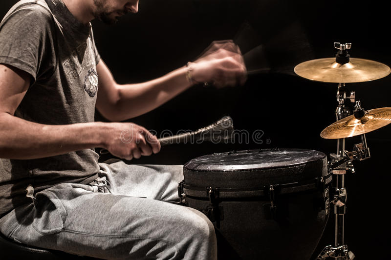 Man playing a djembe drum and cymbals on a black background royalty free stock images